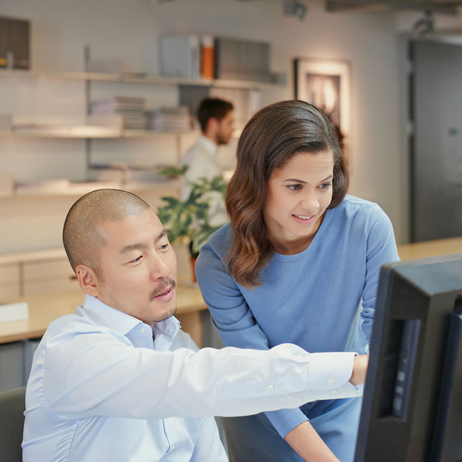 One colleague points out something on a computer screen to another colleague