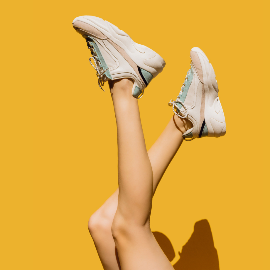 Two legs in the air on a yellow background