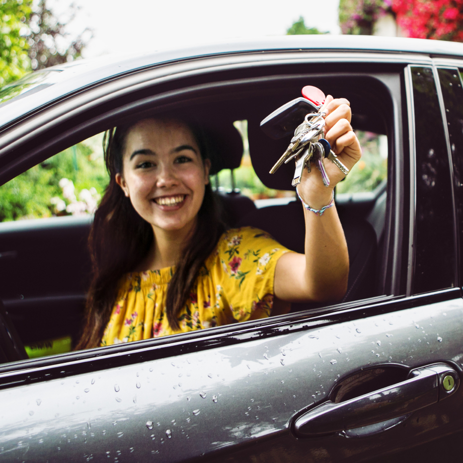 Woman in new car waving keys