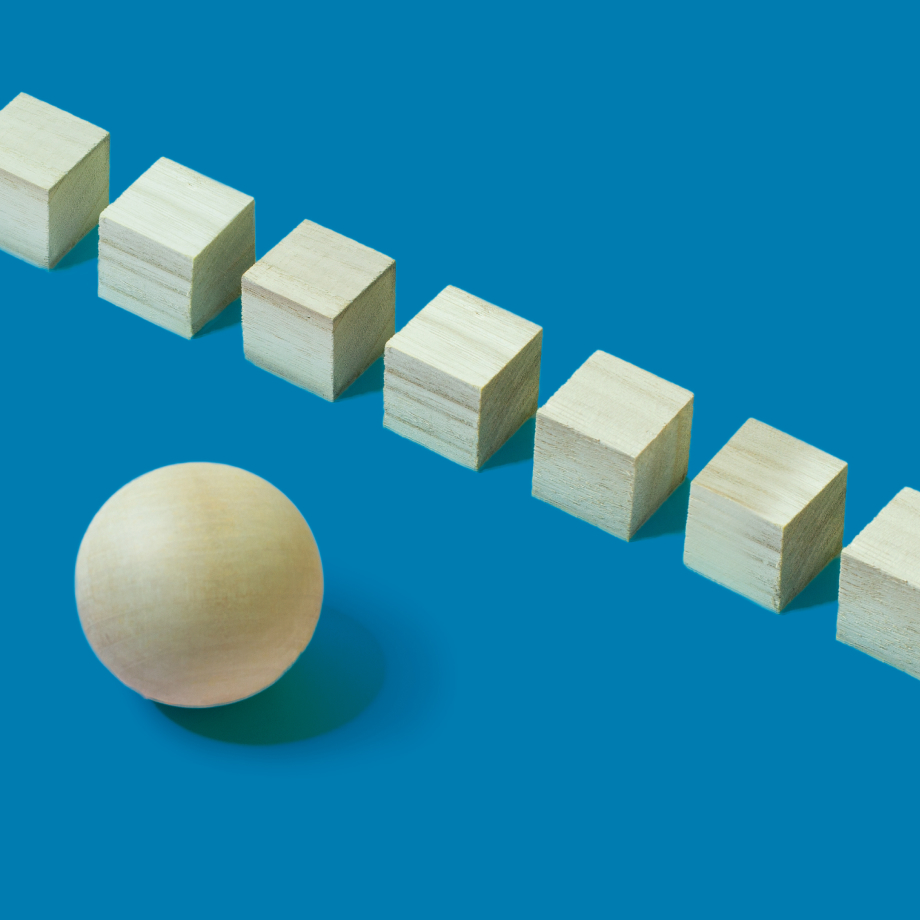 A row of stacks of paper with a big sphere in front of them on a blue background