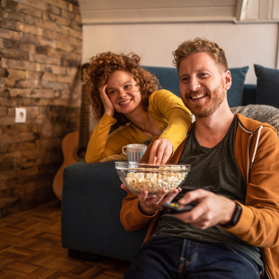 Two friends eating popcorn and watching a movie together