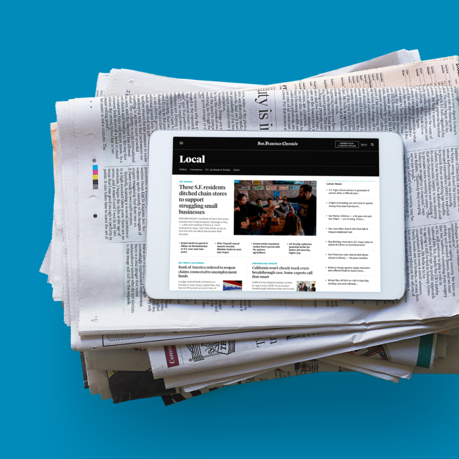 Stack of SF Chronicle paper newspapers topped with an iPad with the digital version