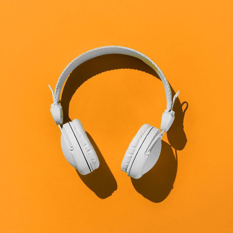 White headphones on an orange background
