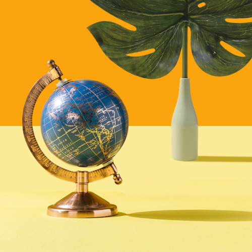 An antique globe resting on a yellow surface and vase with a large, tropical leaf.