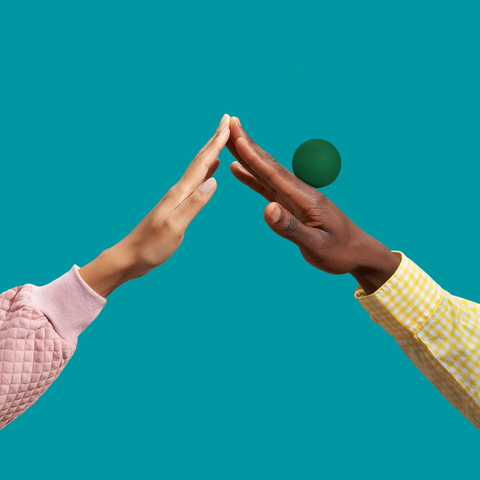 Two hands touching at the fingertips, balancing a ball