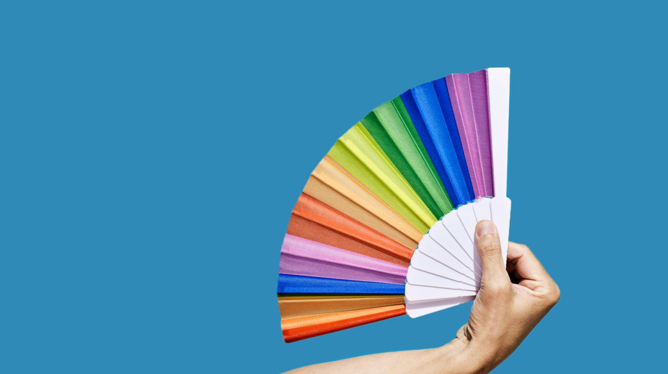 Hand holding multicoloured paper fan