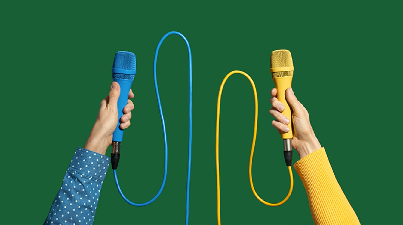 Two hands holding different colored microphones representing leaders discussing the new way of work