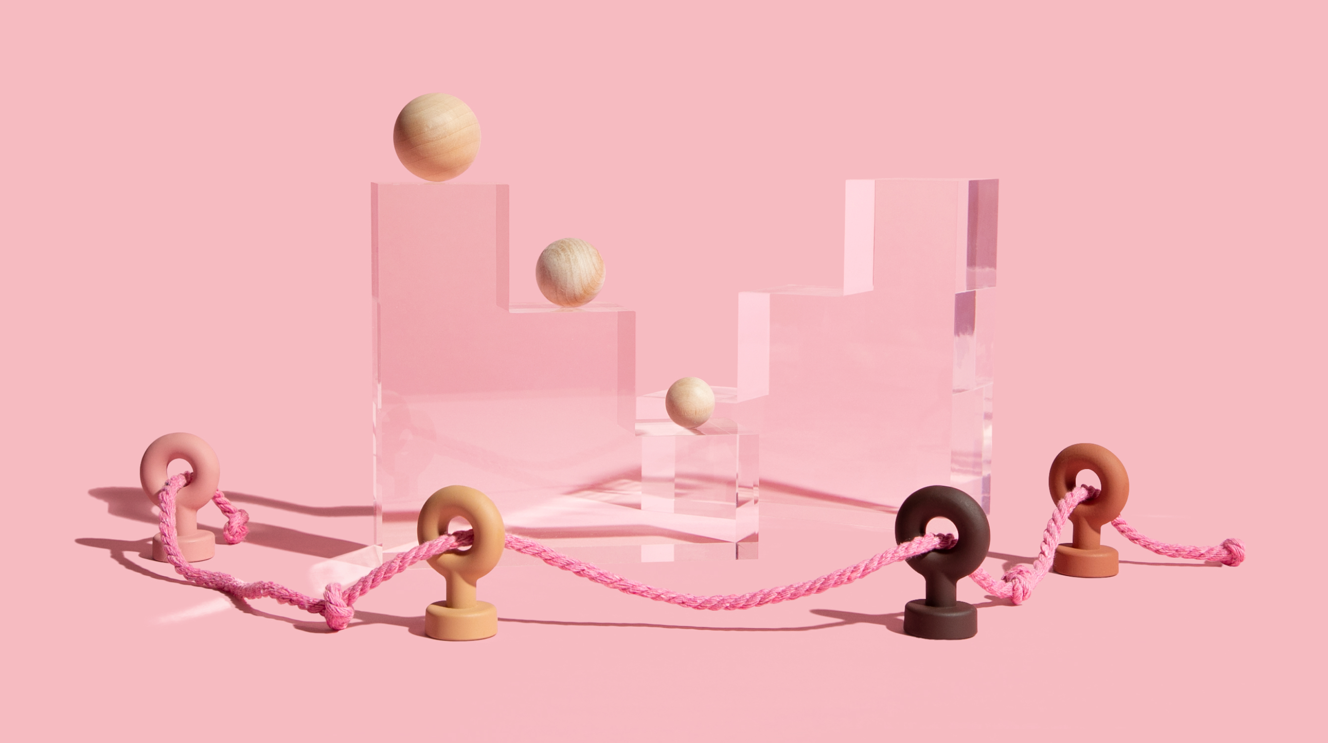 Wooden balls on pedestals with pink rope going through hooks around it