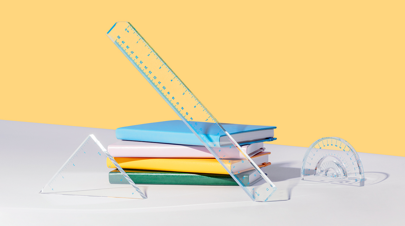 Different types of rulers next to a stack of books