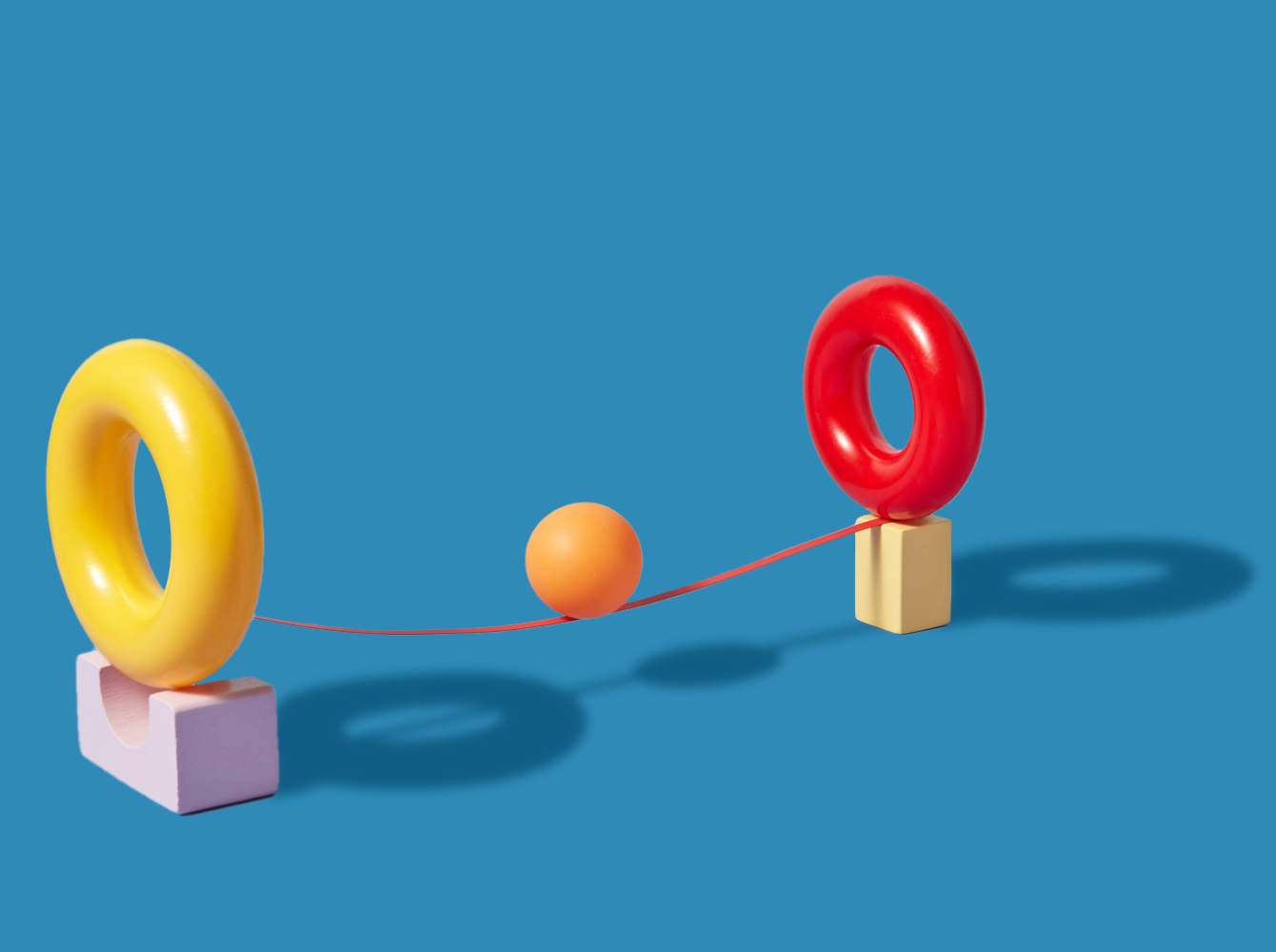 Ball balancing on string between two objects representing teamwork