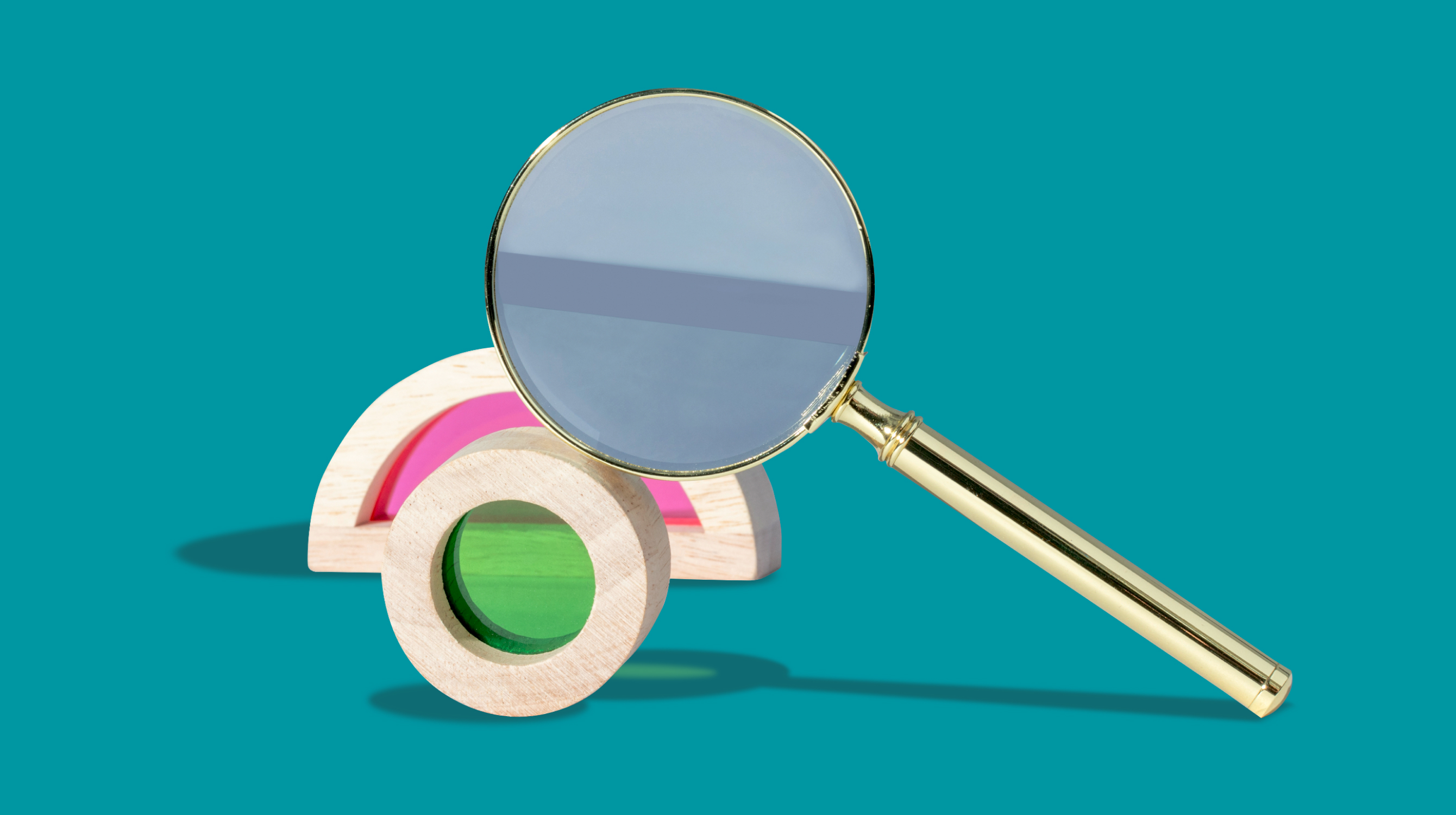 Magnifying glass next to green and pink shapes