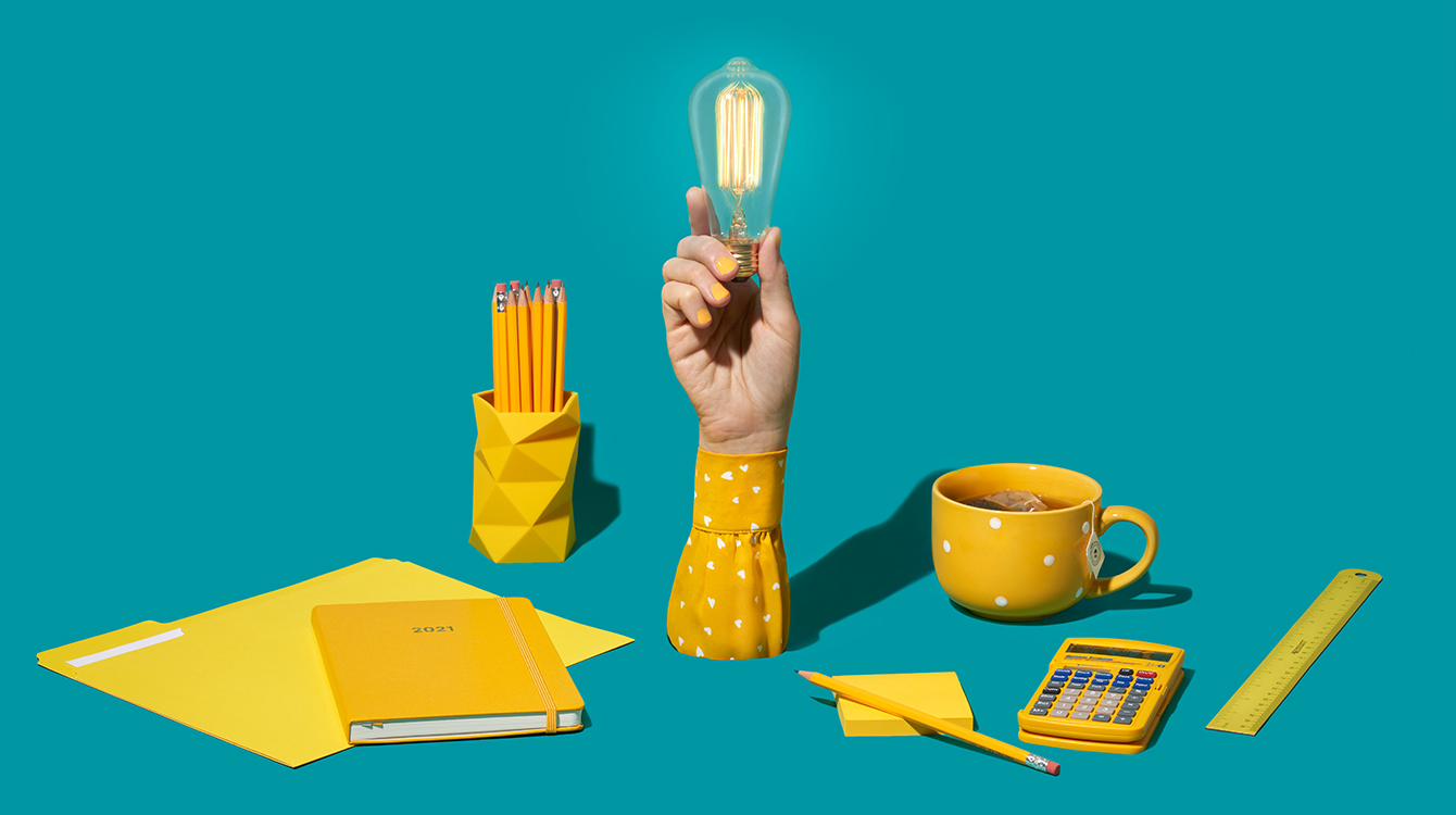 hand holding a light bulb surrounded by work supplies