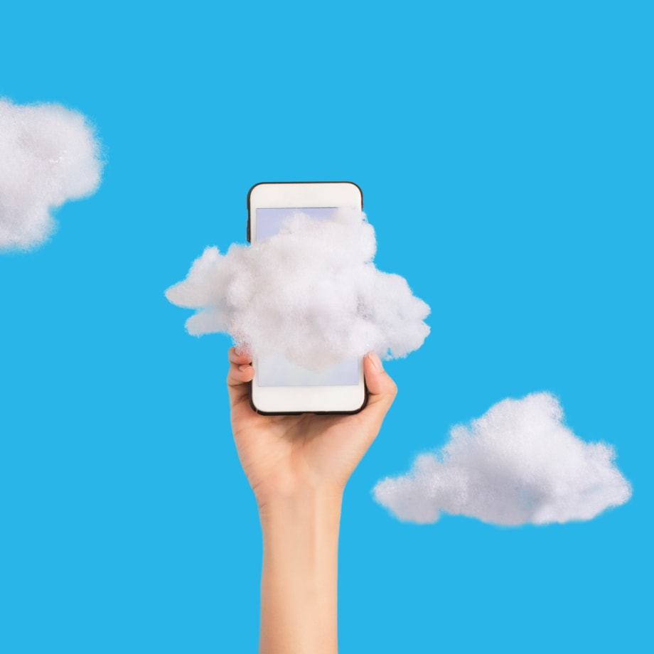 hand holding phone in clouds