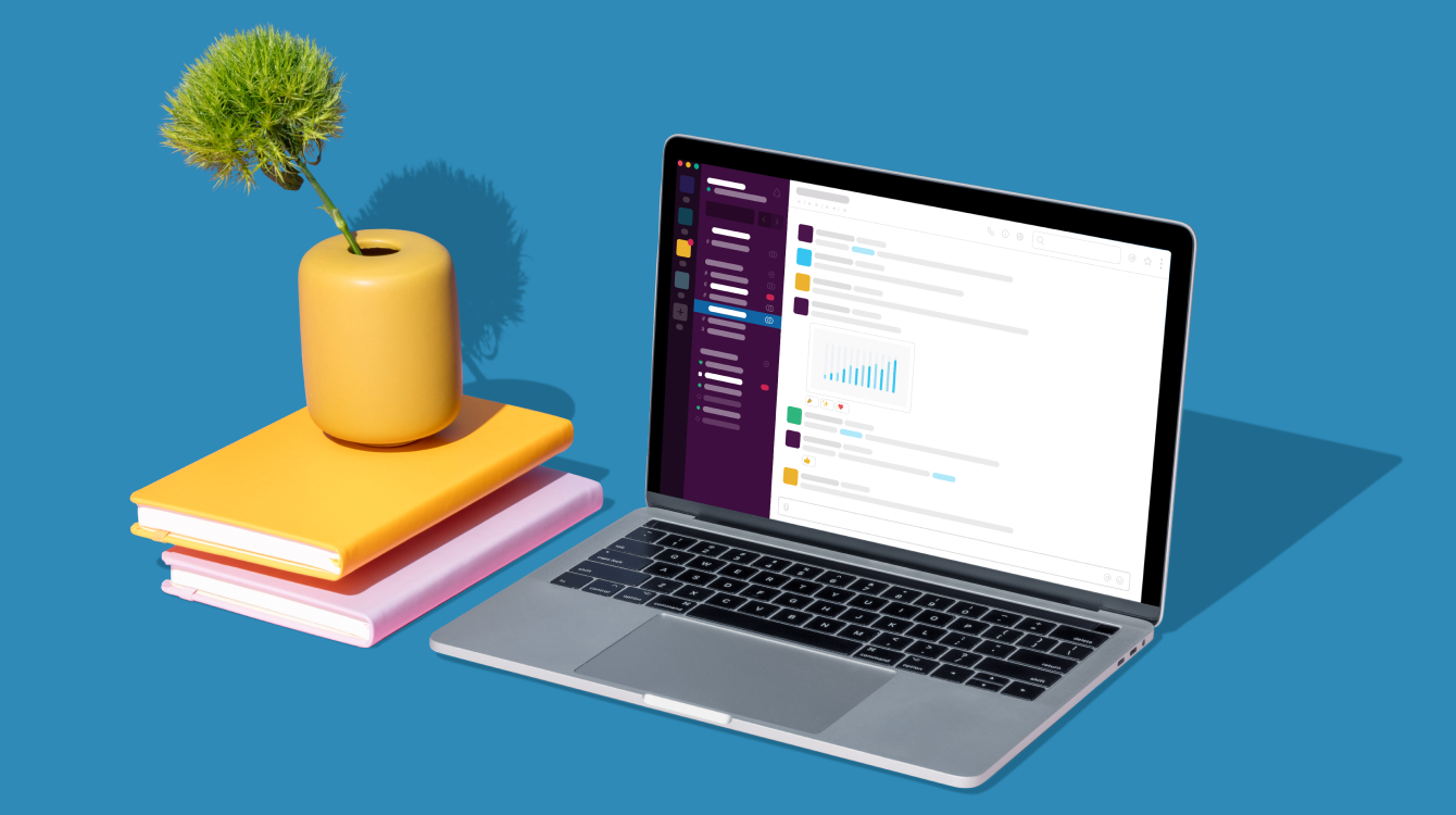 Computer with Slack app opened with books and flower vase on table